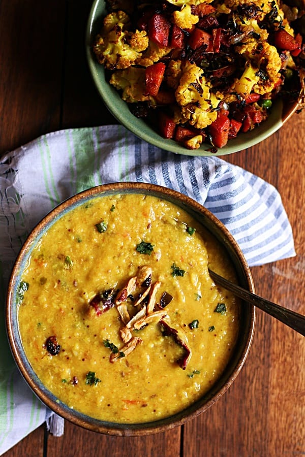 Lasooni dal or garlic flavored lentils served with fried garlic pods in a ceramic bowl with spoons There is a also a serving of sauteed carrots and cauliflower as side dish