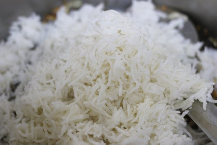 cooked cold rice added to sauteed vegetables in fried rice recipe