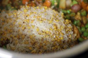 rice and dal added to vegetables