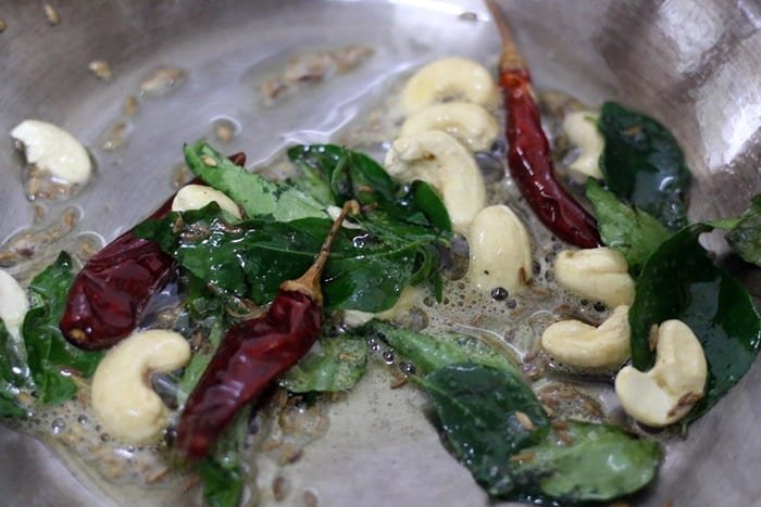 frying curry leaves, red chilies and cashews for bisi bele bath