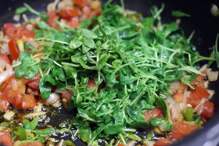 Sautéing tomatoes and fenugreek leaves