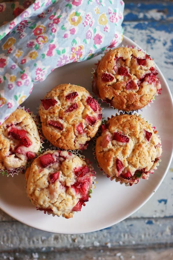 overhead shot of freshly baked strawberry muffins on a white plate.