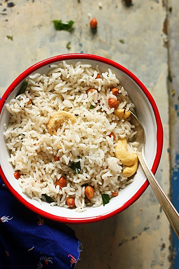 pepper rice served in a red rimmed bowl with a spoon for dinner