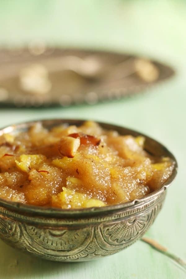 pineapple kesari served warm in a silver bowl.