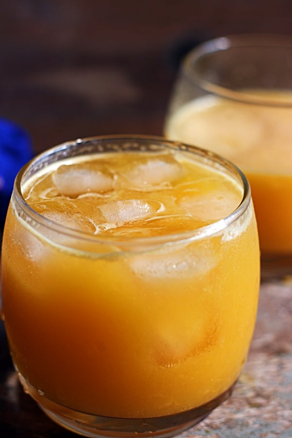 Ganga jamuna juice or orange mosambi juice served chilled with ice cubes in a glass tumbler