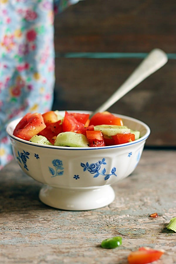 Cucumber tomato salad served in white and blue footed bowl with a spoon.