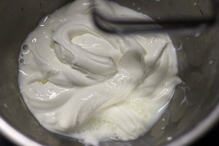 Chilled thick fresh cream added to a mixing bowl for strawberry mousse recipe
