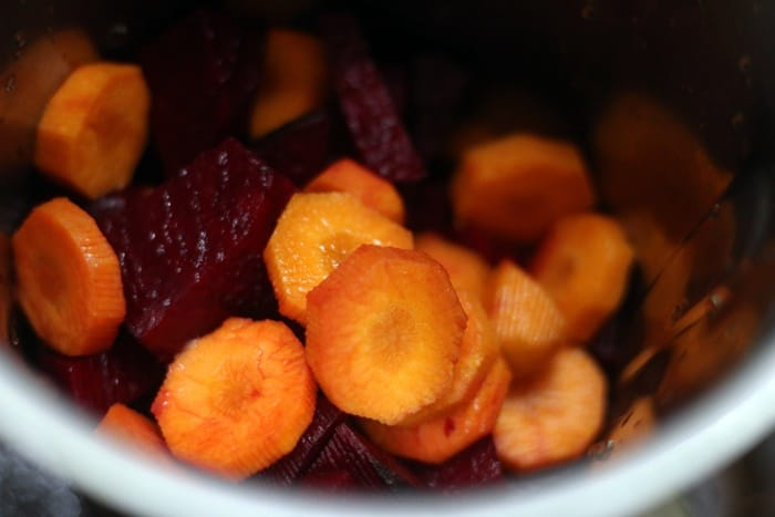 chopped beets and carrots in a blender jar