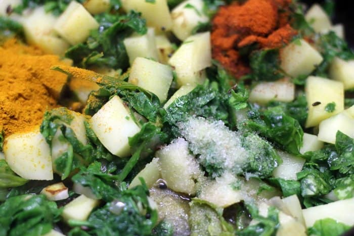 adding spice powders for making aloo palak