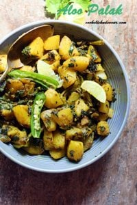 aloo palak served in a grey ceramic bowl.