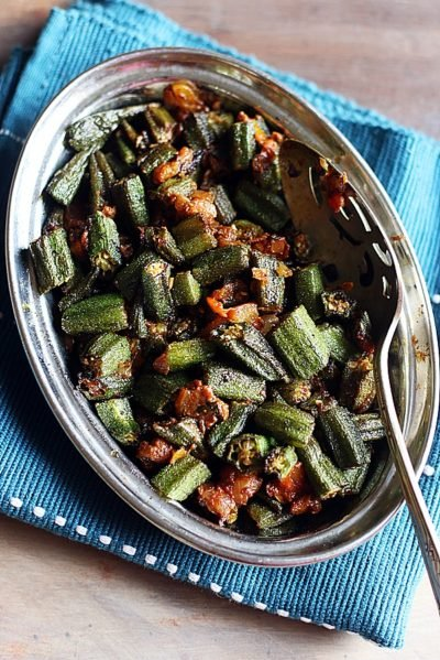 restaurant style bhindi masala served in a steel plate with a spoon