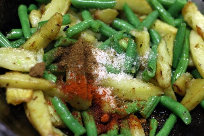 Chopped green beans and spice powders added