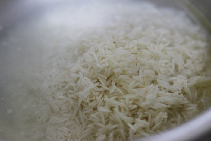 adding soaked and drained basmati rice to boiling water