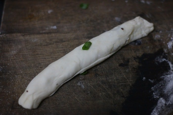 Rolling the dough circle into a tight log