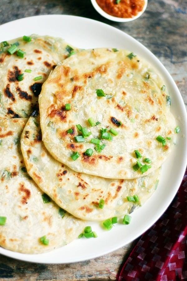 crispy flaky scallion pancakes in a white ceramic plate