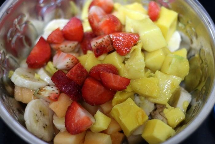 Mixed cut fruits- banana, strawberries and mangoes in a silver bowel.