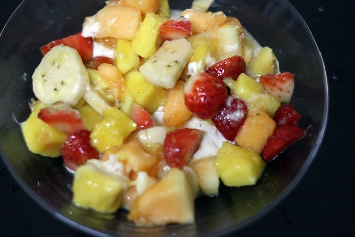 Mixing fruits to whipped cream base.