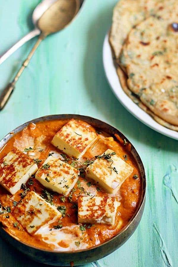 close up shot of paneer butter masala serve with naan in the background