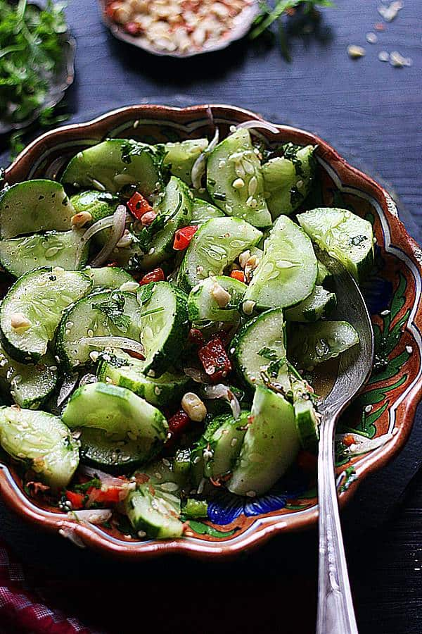 Asian cucumber salad served in a brown footed bowl with a spoon
