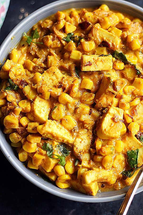 tofu curry with corn served in a grey bowl