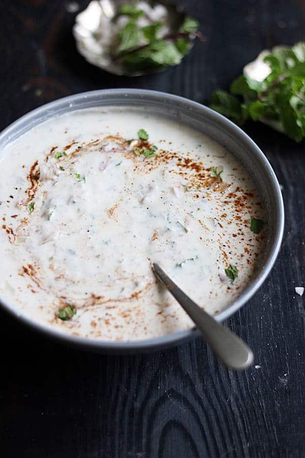 onion raita for biryani in a ceramic bowl