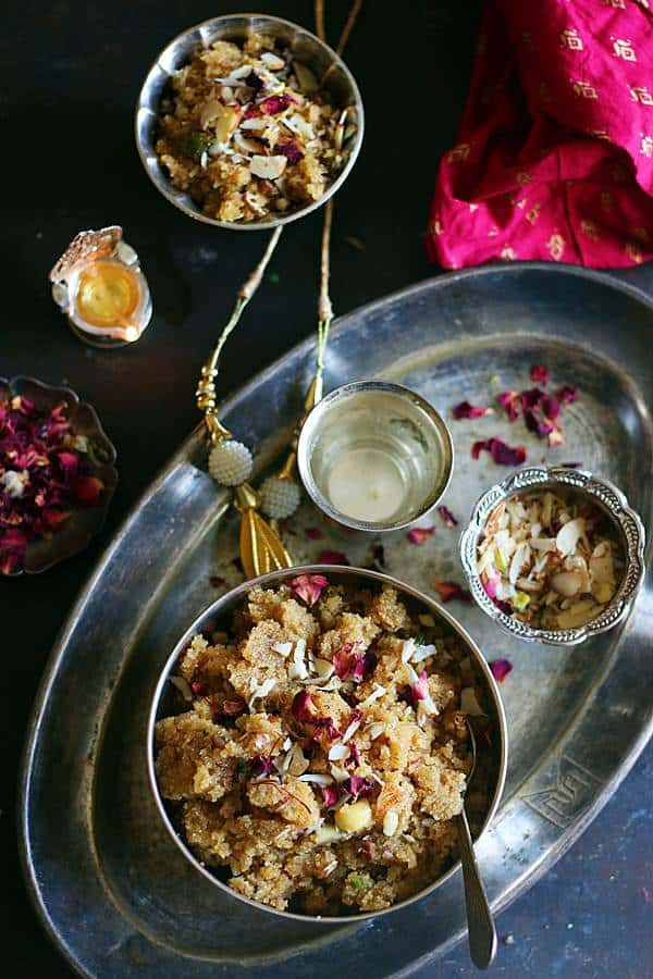 Sooji ka halwa or semolina pudding served with a glass of water in silver tray , dry fruits are placed in a small bowl and a lamp is lit in the background