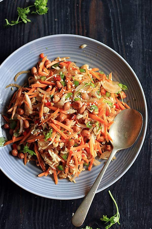 Carrot salas with thai style dressing in a ceramic plate with a spoon.