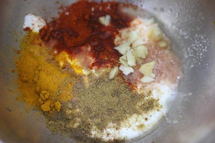 spice powders added to cashew yogurt in a mixing bowl