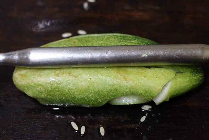 smashing the cucumber with a rolling pin