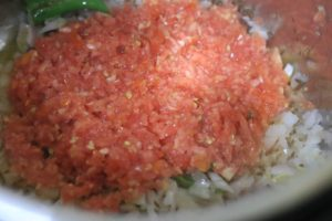 chopped tomatoes added to sauteed onions for making saag chana
