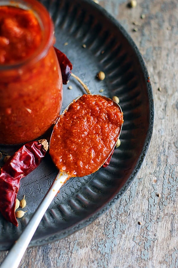 Homemade delicious harissa paste in a spoon with more sauce in a glass jar behind.