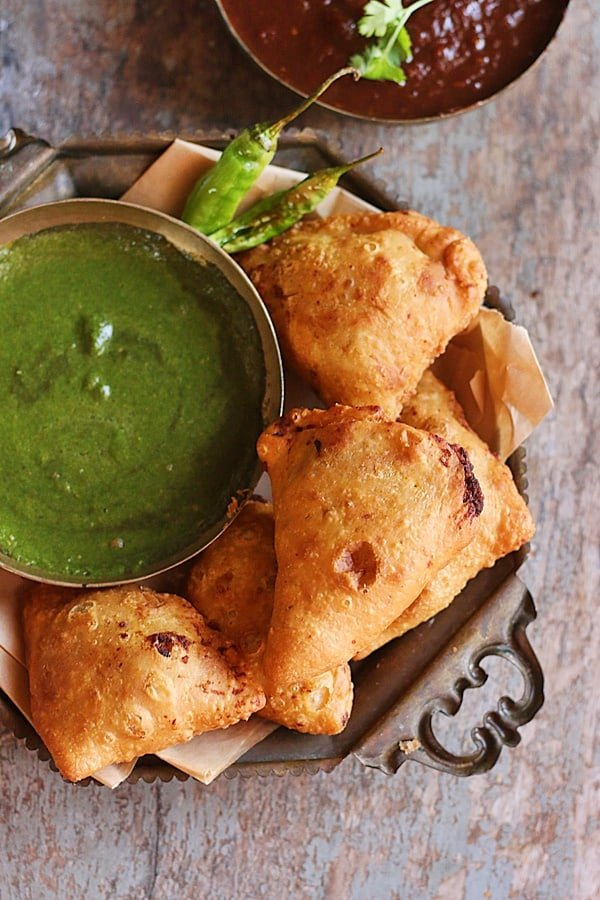 crispy flaky and tasty fresh homemade samosa served with green chutney and tamarind chutney