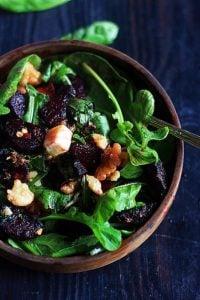 arugula beet salad served in a wooden salad bowl.