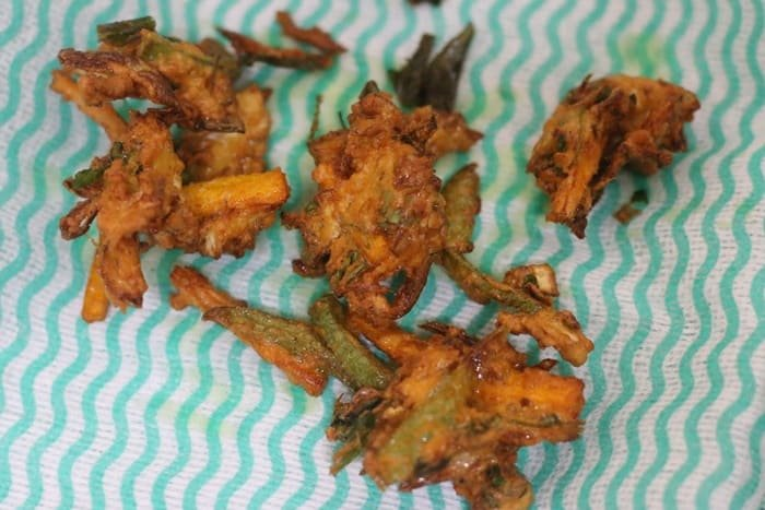 draining excess oil from fried pakoras