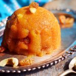 Homemade rava kesari served in a silver plate garnished with cashews and raisins
