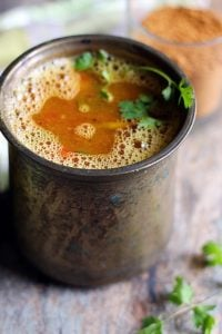 frothy homemade tomato rasam in a tall brass vessel