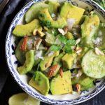 close up of cucumber avocado salad in a blue ceramic bowl