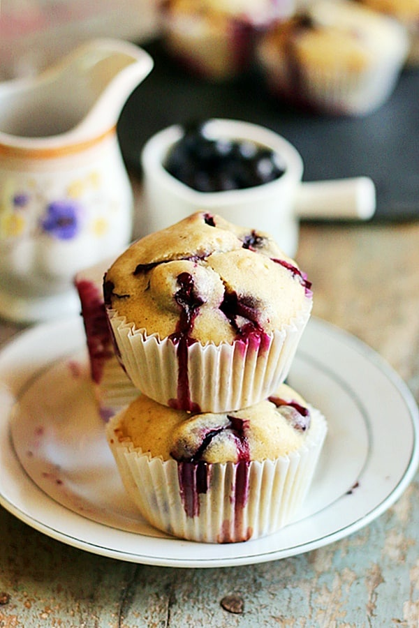 Stack of eggless blueberry muffins in a small dessert plate with more blueberries & coffee in background