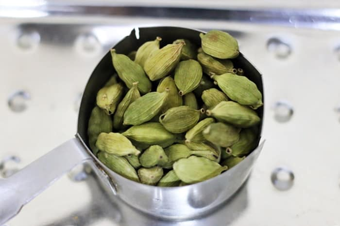 cleaned green cardamom pods in a measuring cup