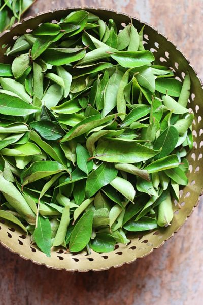 Fresh curry leaves in a brass bowl.