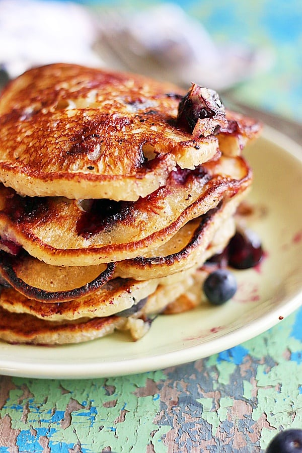 closeup shot of homemade vegan blueberry pancakes served in a ceramic plate