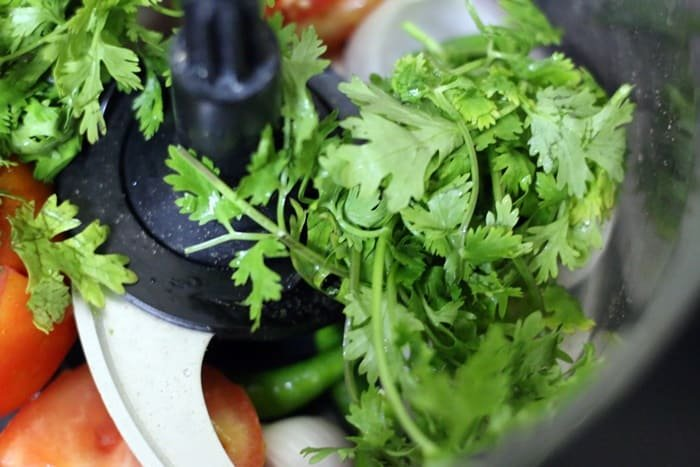 chopping vegetables in food processor for making corn chaat recipe